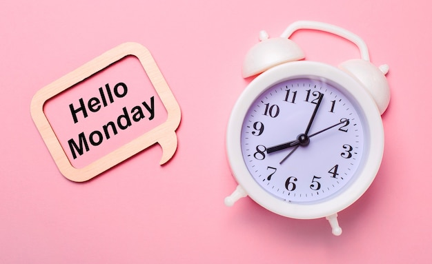 На нежном розовом фоне белый будильник и деревянная рамка с надписью hello monday.