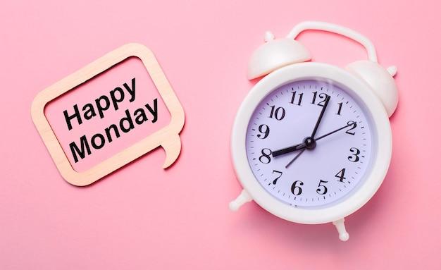 繊細なピンクの背景に、白い目覚まし時計と「hellomonday」の文字が書かれた木製のフレーム