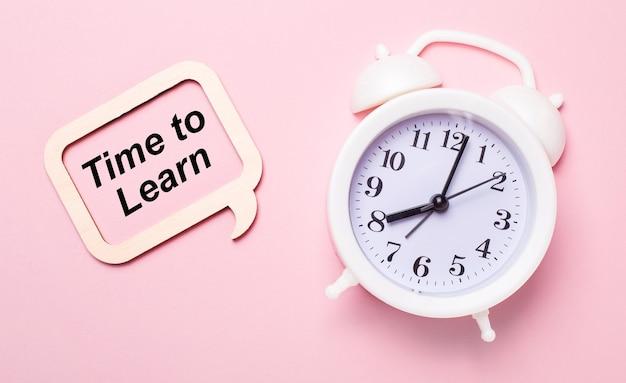 繊細なピンクの背景に、白い目覚まし時計と「学習する時間」というテキストが書かれた木製のフレーム
