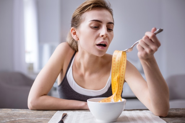 На диете. симпатичная молодая женщина сидит за столом во время диеты