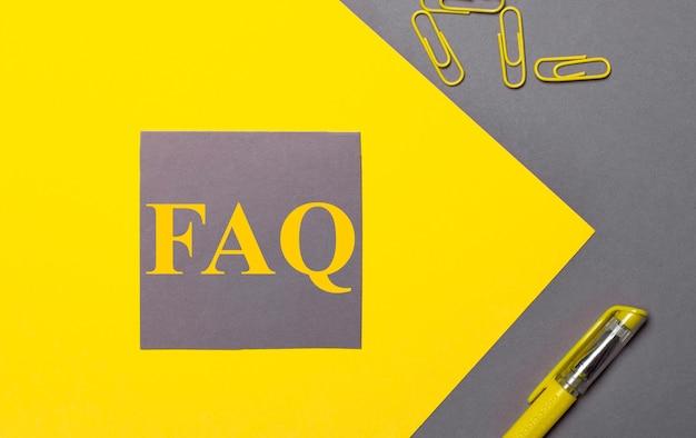 灰色と黄色の背景に、黄色のテキストに関するよくある質問、黄色のペーパークリップ、黄色のペンが付いた灰色のステッカー