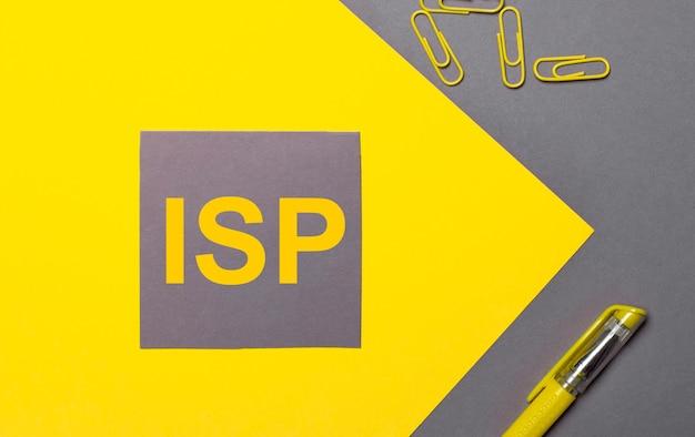 На серо-желтом фоне серая наклейка с желтым текстом isp internet service provider, желтые скрепки и желтая ручка.
