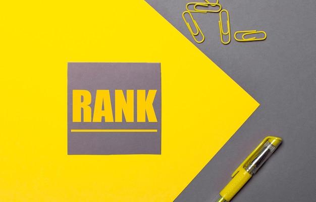 На серо-желтом фоне серая наклейка с желтым текстом rank, желтые скрепки и желтая ручка.