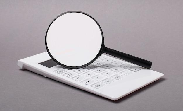 灰色の背景に、黒い電卓とテキストを挿入する場所のある虫眼鏡。ビジネスコンセプト