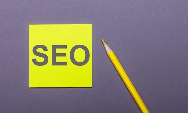На сером фоне ярко-желтый карандаш и желтая наклейка со словом seo search engine optimization.