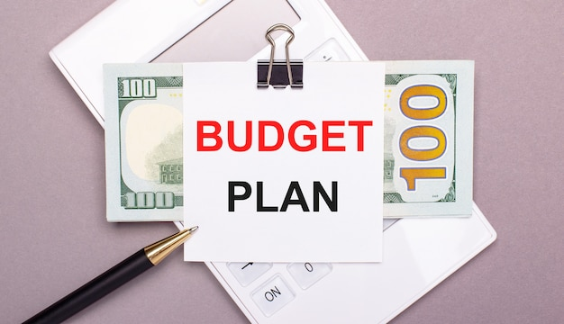 На сером фоне белый калькулятор, ручка, банкноты и лист бумаги под черной скрепкой с текстом budget plan. бизнес-концепция
