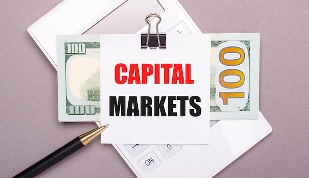 На сером фоне белый калькулятор, ручка, банкноты и лист бумаги под черной скрепкой с надписью capital markets. бизнес-концепция