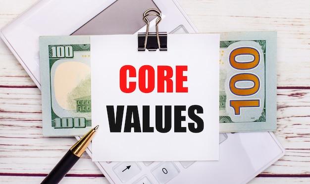 На сером фоне белый калькулятор, ручка, банкноты и лист бумаги под черной скрепкой с текстом основные ценности. бизнес-концепция