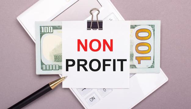 На сером фоне белый калькулятор, ручка, банкноты и лист бумаги под черной скрепкой с надписью non profit. бизнес-концепция