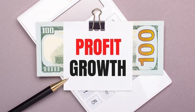 На сером фоне белый калькулятор, ручка, банкноты и лист бумаги под черной скрепкой с текстом рост прибыли. бизнес-концепция
