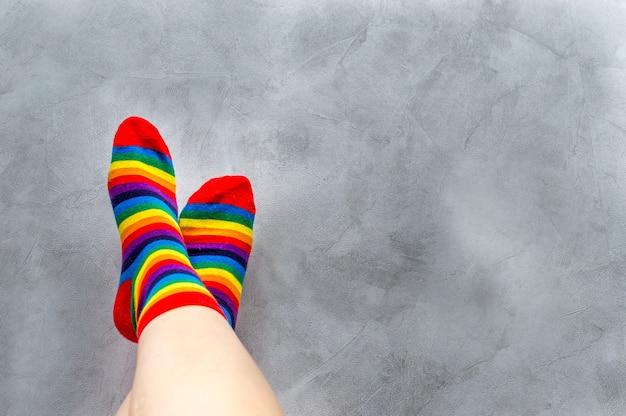 灰色の背景に、マルチカラーの靴下を履いた男の足のクローズアップ。虹。シンボル。コンセプトlgbt