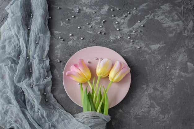 ピンクのプレートの灰色の背景にピンクのチューリップと灰色の真珠です。