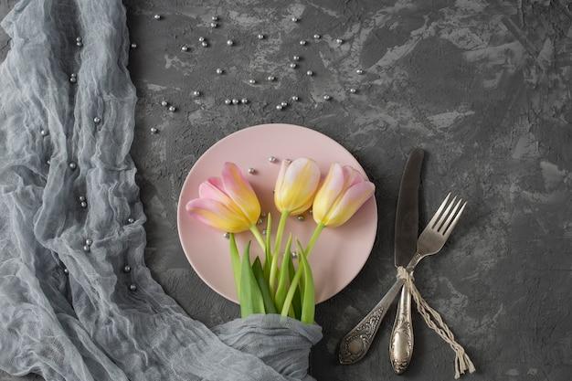 ピンクのプレートの灰色の背景にピンクのチューリップ、灰色の真珠、カトラリー - ナイフとフォークがあります