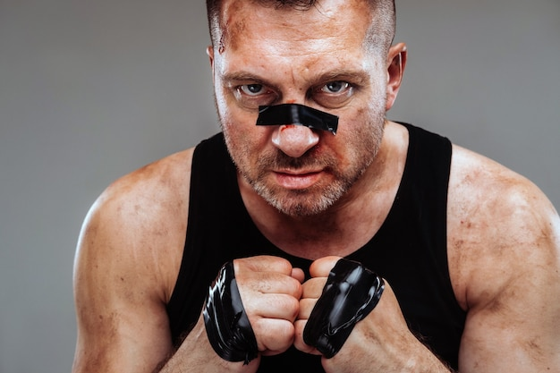 회색 배경에 전투기처럼 보이고 싸움을 준비하는 검은 티셔츠에 폭행당한 남자를 의미합니다