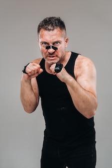 На сером фоне стоит избитый мужчина в черной футболке, похожий на бойца и готовящийся к бою.