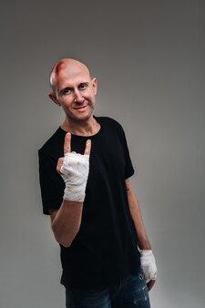 На сером фоне стоит избитый мужчина в черной футболке со скрученными руками.