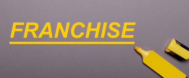 На сером фоне желтый маркер и желтая надпись franchise.