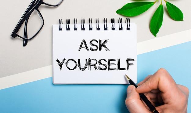 灰色がかった青色の背景に、眼鏡と植物の緑の葉の近くで、男性が一枚の紙に「自分に尋ねる」というテキストを書きます。