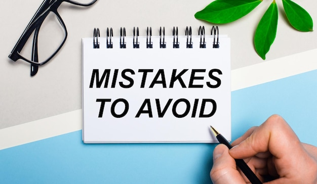 灰色がかった青色の背景、眼鏡の近く、植物の緑の葉の上に、男性が一枚の紙に「避けるべき間違い」というテキストを書いています。フラットレイ。上からの眺め。