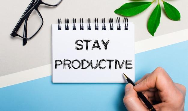 회색 파란색 배경, 안경 및 식물의 녹색 잎 근처에 한 남자가 종이에 '생산성 유지'라는 텍스트를 씁니다.