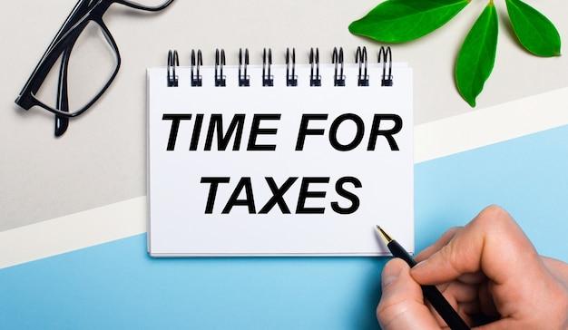На серо-голубом фоне возле очков и зеленого листа растения мужчина пишет на листке бумаги текст «время налоги». плоская планировка. вид сверху.