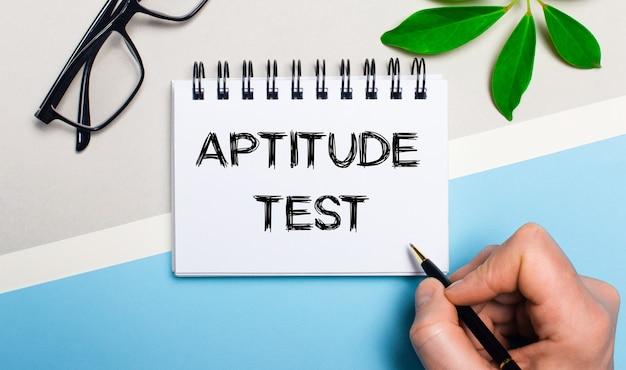 眼鏡と植物の緑の葉の近くの灰青色の表面に、男性が一枚の紙に「適性検査」というテキストを書きます。