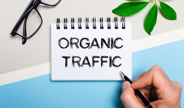 На серо-голубой поверхности возле очков и зеленого листа растения мужчина пишет на листе бумаги текст organic traffic