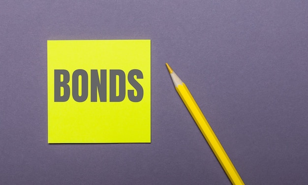 На серой поверхности ярко-желтый карандаш и желтая наклейка со словом bonds.