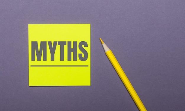 灰色の表面に、明るい黄色の鉛筆とmythsという単語が書かれた黄色のステッカー