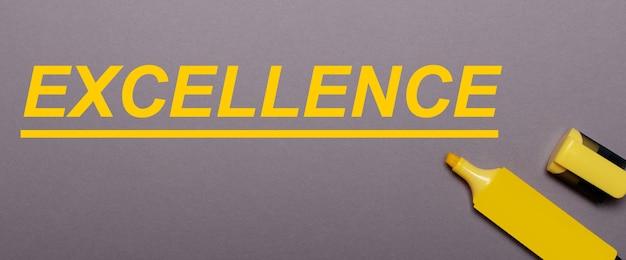 회색 표면에 노란색 마커와 노란색 비문 excellence