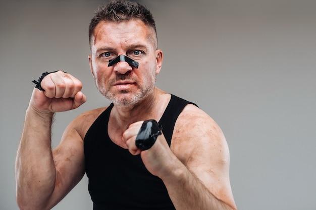 На серой стене изображен избитый мужчина в черной футболке, похожий на бойца и готовящийся к бою.