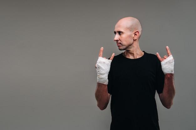 На серой стене избитый мужчина в черной футболке со скрещенными руками.