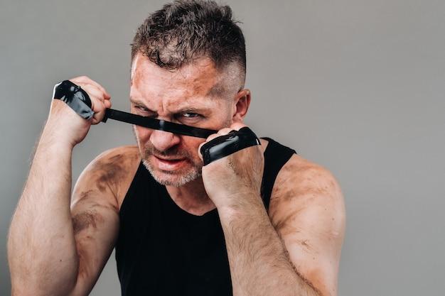 На серой стене стоит избитый мужчина в черной футболке, готовящийся к драке.
