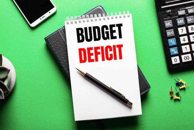 На зеленом фоне телефон, калькулятор и дневник с надписью budget deficit.