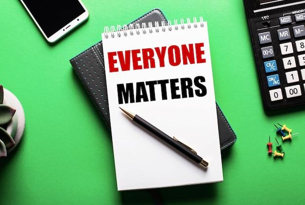 녹색 배경-everyone matters라는 비문이있는 전화, 계산기 및 일기
