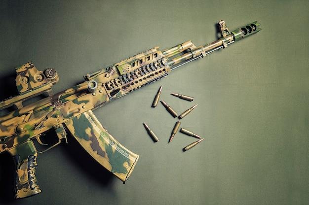 緑の背景には、弾丸と一緒にカモフラージュ機関銃があります。上からの眺め。戦争、政治的紛争の概念。