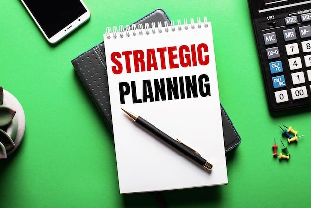 На зеленой поверхности - телефон, калькулятор и дневник с надписью стратегическое планирование.