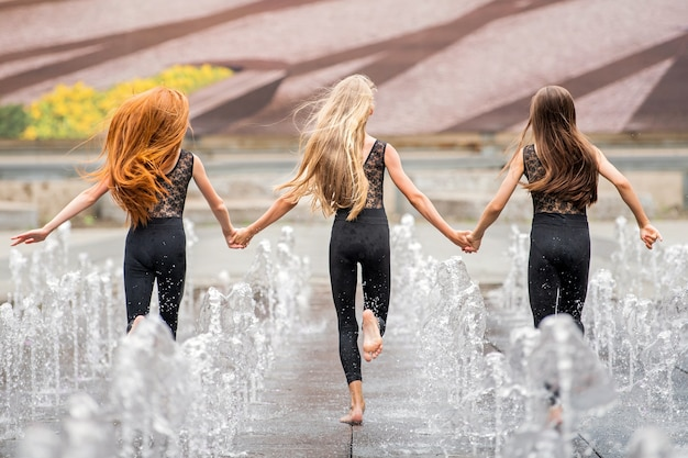 더운 날 검은색 바디콘 수트를 입은 세 명의 작은 발레리나들이 더운 날 도시 경관을 배경으로 튀는 분수 사이를 달리고 있습니다.
