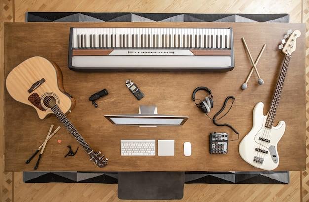 На большом деревянном столе лежит акустическая гитара, бас-гитара, музыкальные клавиши, палки, наушники с микшером, кападастр и компьютер.