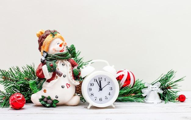 明るい背景に、美しい雪だるま、白い目覚まし時計、新年のボールとギフトが付いたモミの木の枝。クリスマスのコンセプト。スペースをコピーします。