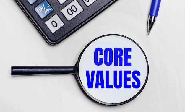 На светлом фоне черный калькулятор, синяя ручка и увеличительное стекло с текстом внутри слова core values. вид сверху