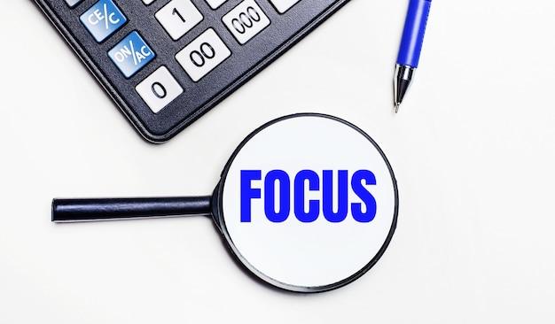На светлом фоне черный калькулятор, синяя ручка и увеличительное стекло с текстом внутри слова focus. вид сверху