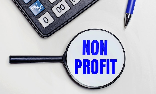 На светлом фоне черный калькулятор, синяя ручка и увеличительное стекло с текстом внутри слова non profit. вид сверху