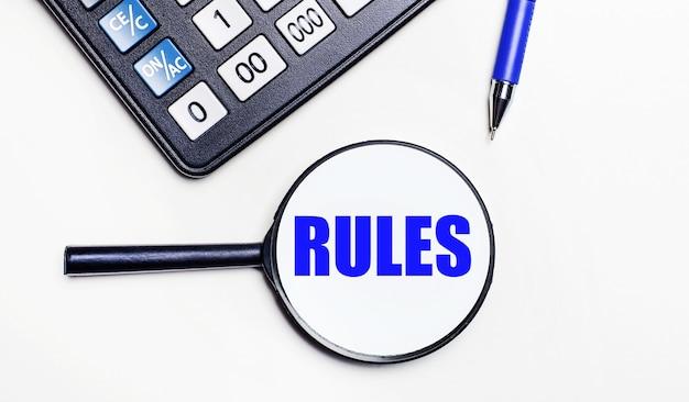 На светлом фоне черный калькулятор, синяя ручка и увеличительное стекло с текстом внутри слова правила. вид сверху
