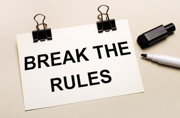 На светлом фоне черный открытый маркер и на черных зажимах белый лист бумаги с текстом break the rules