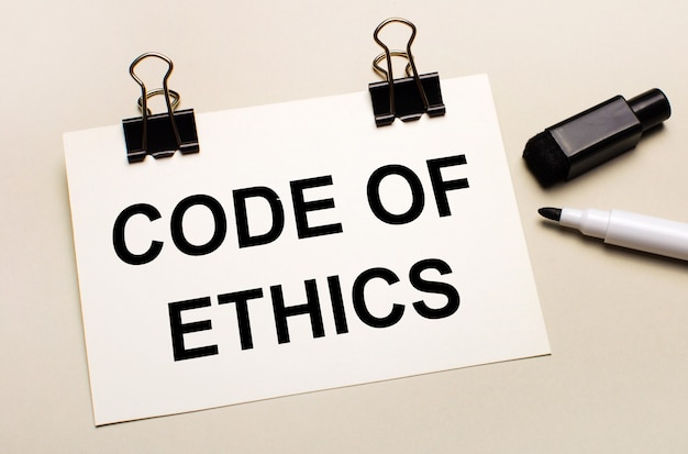 На светлом фоне черный открытый маркер и на черных зажимах белый лист бумаги с текстом кодекс этики.
