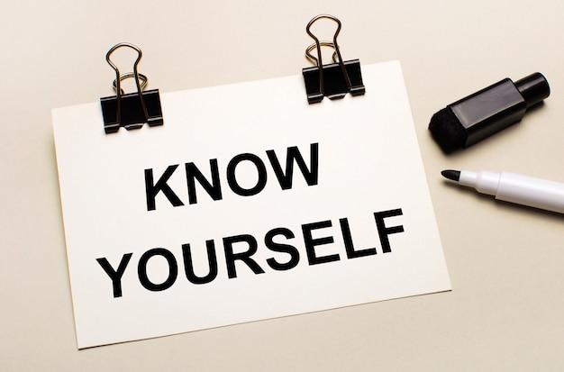 明るい背景には、黒いオープンマーカーがあり、黒いクリップには、「knowyourself」というテキストが付いた白い紙があります。