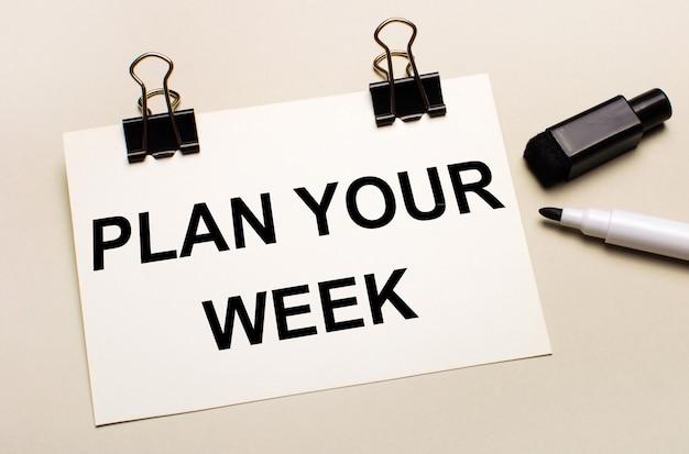 明るい背景には、黒いオープンマーカーがあり、黒いクリップには、「plan yourweek」というテキストが付いた白い紙があります。