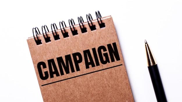 На светлом фоне черная ручка и коричневая тетрадь на черных пружинах с надписью кампания.