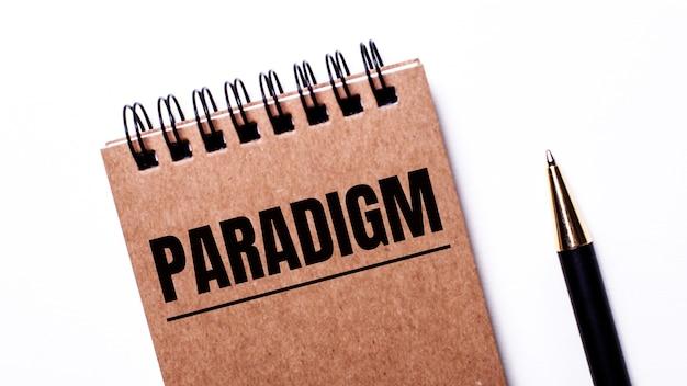 На светлом фоне черная ручка и коричневая тетрадь на черных пружинах с надписью paradigm.